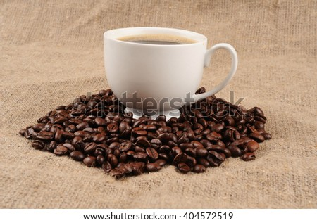 coffee beans with mug on a rough sacking