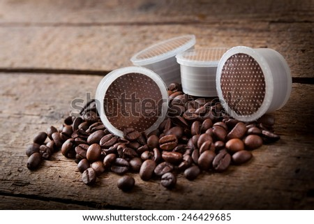 Coffee beans with pods on wooden table. - stock photo