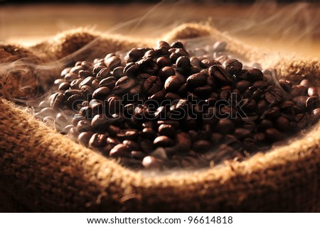Coffee beans with smoke in a bag. - stock photo