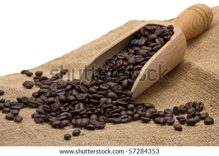 Coffee beans with wooden scoop on burlap bag - stock photo