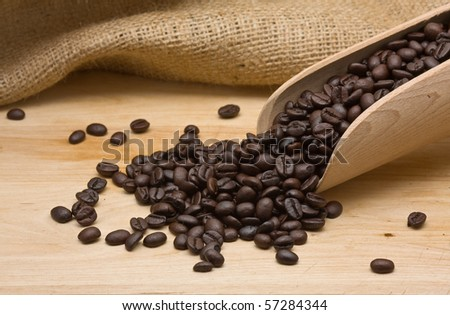 Coffee beans with wooden scoop on wood - stock photo