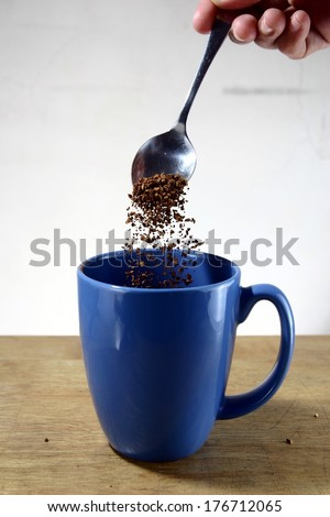 Coffee Being Poured To a Mug Photo of coffee grains being poured to a blue mug. - stock photo