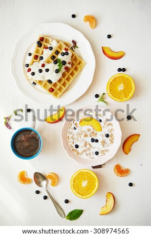 coffee, belgium waffles, corn flakes with milk and fruits. top view