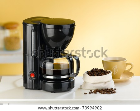 Coffee blender and boiler with coffee seeds in a kitchen interior - stock photo