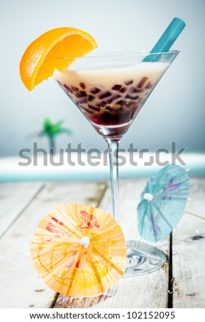 Coffee Boba Tea with sweet ingredients and milk in front of the ocean - stock photo