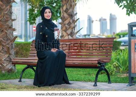 Coffee break . Arab businesswomen in hijab holding a cup of coffee outside on the background of skyscrapers in Dubai and looking at the camera. The woman is dressed in a black abaya - stock photo
