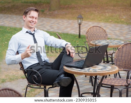 Coffee break. Attractive young caucasian businessman in shirt and tie working on laptop while relaxing in sidewalk cafe smiling at the camera holding cup of coffee - stock photo
