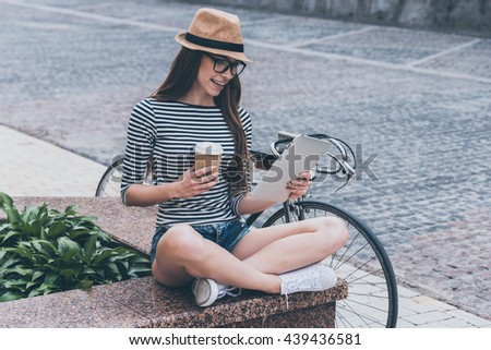 Coffee break.  Beautiful young smiling woman looking at her digital tablet and holding coffee cup while sitting on the bench near her bicycle  - stock photo
