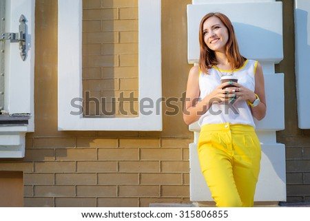 Coffee break. Beautiful young woman holding paper cup while leaning on wall. - stock photo