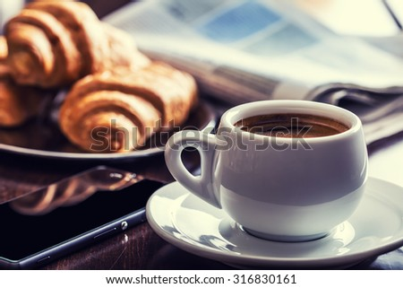 Coffee break business. Cup of coffee mobile phone and newspaper. - stock photo