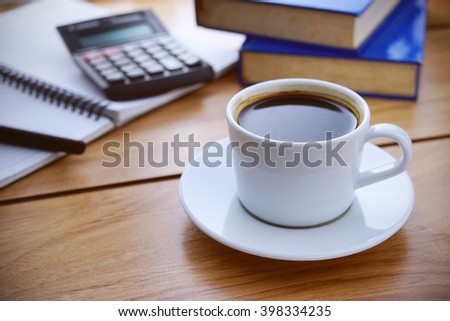 Coffee break concept.Notepad, books and calculator on wooden table. Warm tone with soft selective focus, shallow depth of field.