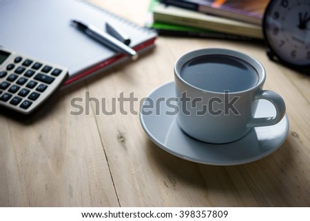 Coffee break concept.Notepad, books, clock and calculator on wooden table.Dim light tone with soft selective focus, shallow depth of field. - stock photo