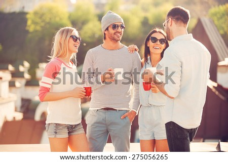 Coffee break. Four young cheerful people chatting and drinking coffee while standing on the roof terrace together - stock photo