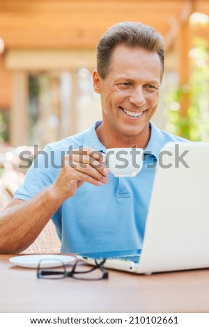 Coffee break in cafe. Cheerful mature man drinking coffee and looking at laptop with smile while sitting at the table outdoors with house in the background  - stock photo