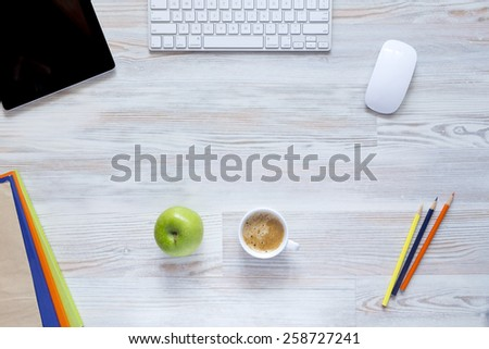 Coffee break. Well organized workspace on the wooden table with tablet PC, keyboard and mouse, color pencils, coffee mug along with green apple and some booklets - stock photo