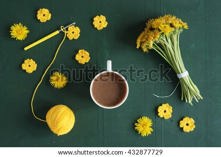 Coffee, bunch of dandelions and crocheted flowers.