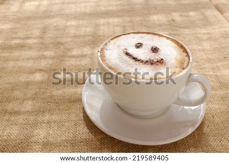 Coffee cappuccino with foam or chocolate smiling welcome happy face in restaurant or hotel - stock photo