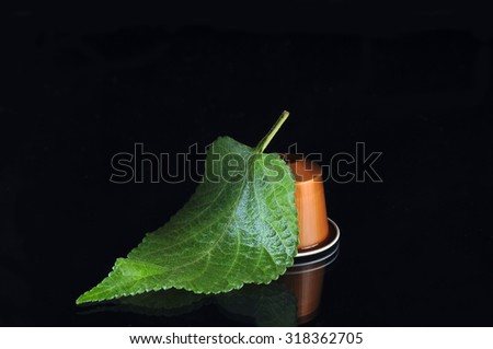 coffee capsule and green leaf isolated on black background - stock photo