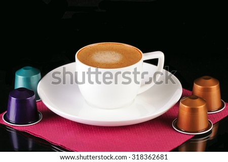 coffee capsules and white cup isolated on black background - stock photo