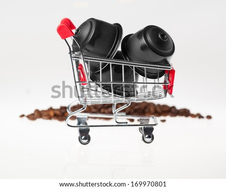 Coffee capsules in a small shopping cart on white background. - stock photo