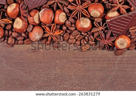 Coffee, chocolate, star anise and hazelnuts on a  wooden  background - stock photo