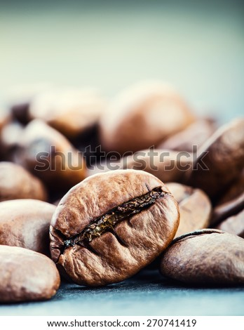 Coffee. Coffee beans. Roasted coffee beans spilled freely on a table.Coffee time - stock photo