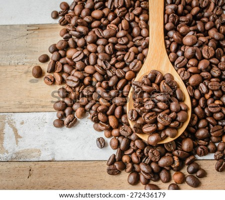 Coffee crop beans on bamboo spoon and wooden background - stock photo