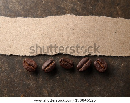 Coffee crop beans with paper on wood texture background - stock photo