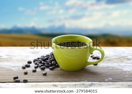 Coffee cup above blurred mountain range - stock photo
