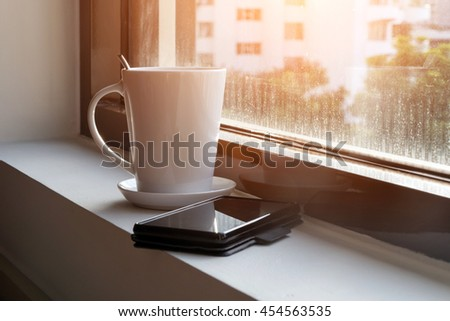 Coffee cup against window  - stock photo
