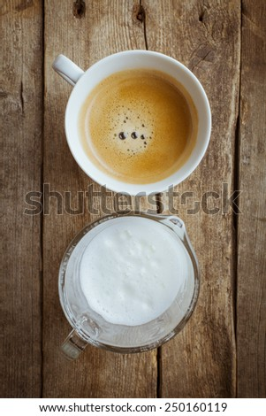 Coffee cup and a jar with milk on a wooden background - stock photo