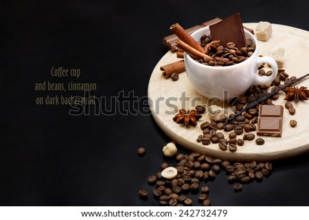 Coffee cup and beans, cinnamon on dark background - stock photo