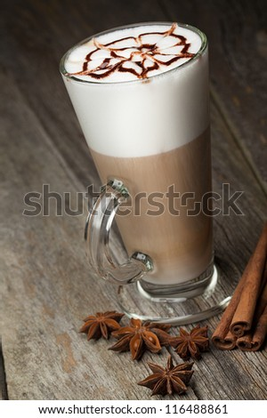 coffee cup and beans, cinnamon sticks, nuts and chocolate on wooden table on brown background - stock photo