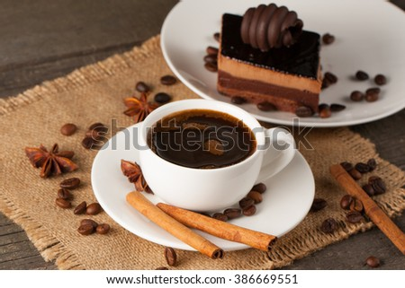 Coffee cup and beans on a rustic background. Coffee Espresso and a piece of cake with a curl. Cup Of Coffee and coffee beans on table. - stock photo