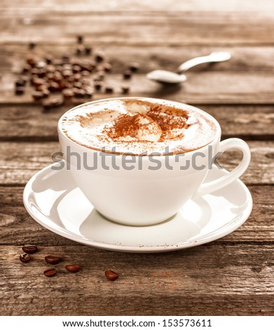 Coffee cup and beans on an old vintage planked wood table - moody still life - stock photo