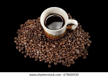 Coffee cup and beans on black background - stock photo