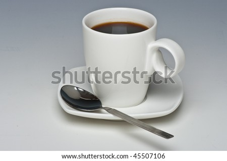 Coffee cup and black coffee against graduated background