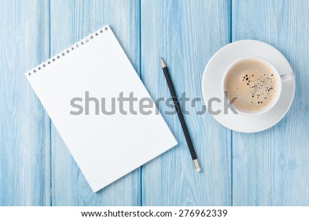 Coffee cup and blank notepad over blue wooden table. Top view with copy space - stock photo