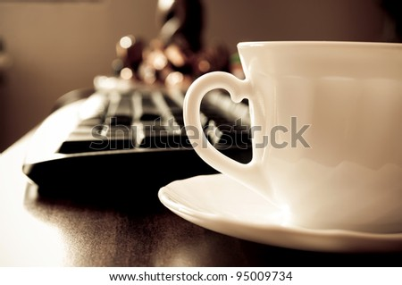 Coffee cup and blurred computer keyboard in the background - stock photo