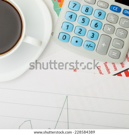 Coffee cup and calculator over financial documents - stock photo