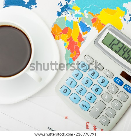 Coffee cup and calculator over world map and financial charts - 1 to 1 ratio