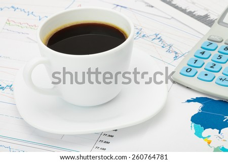 Coffee cup and calculator over world map and some financial charts - business concept - stock photo