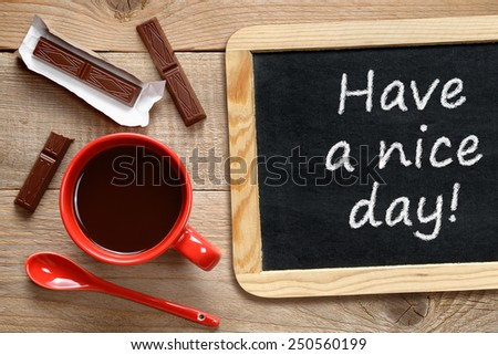 Coffee cup and chalkboard with phrase Have a nice day! - stock photo