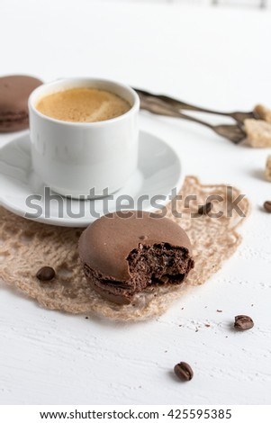 Coffee Cup and chocolate French macaroons on a white wooden background. Selective focus.