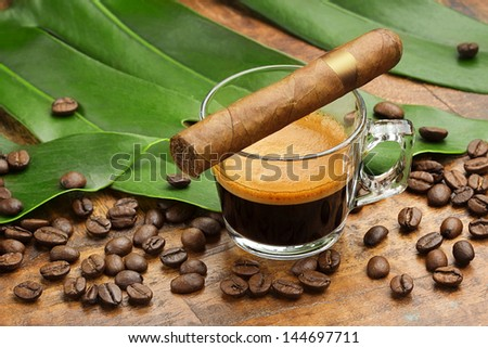 coffee cup and cigar, coffee beans and leaves on wooden background - stock photo