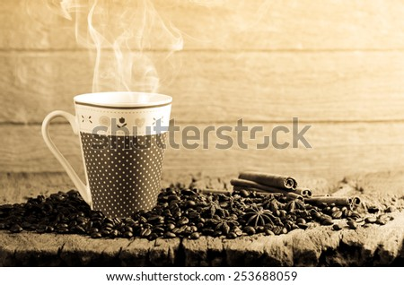 Coffee cup and coffee beans around on wooden table - stock photo