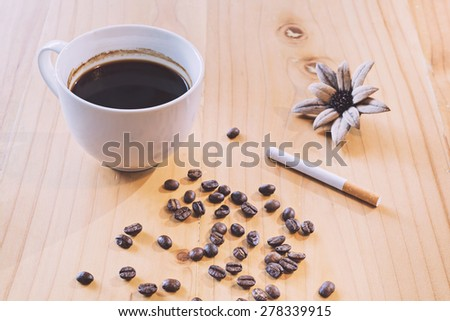 Coffee cup and Coffee beans, cigarette on a wooden table in vintage tone color style, selective focus  (detailed close-up shot) - stock photo
