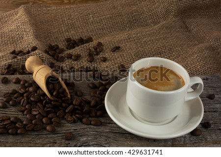 Coffee cup and coffee beans. Cup of strong morning coffee and coffee grains on the sackcloth