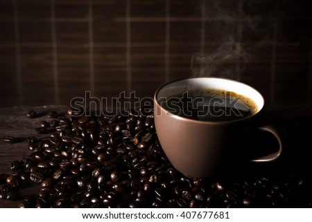 Coffee cup and coffee beans on a wood background. - stock photo
