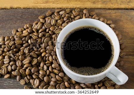 coffee cup and coffee beans on old wood - stock photo